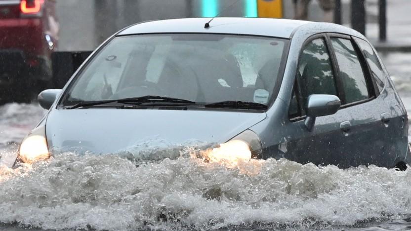 Ein Auto fährt durch eine überschwemmte Straße in London.